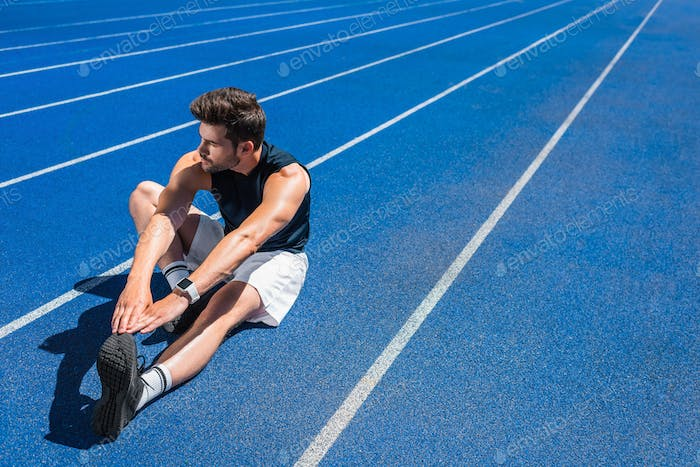 handsome young man stretching on running track