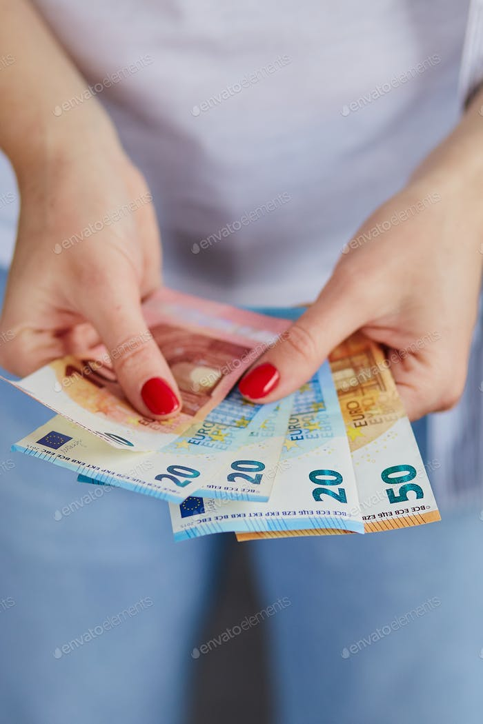 A woman is holding euro money in her hands.