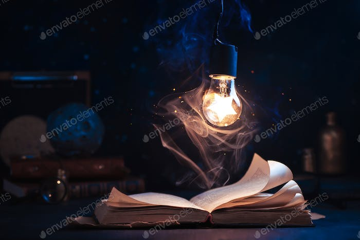 An open book with lighting by a star inside a lightbulb