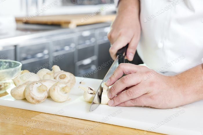 Professional chef cutting mushrooms in the kithcen