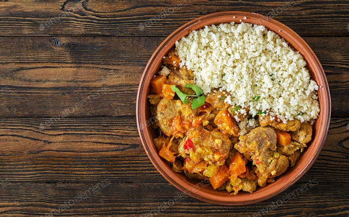 Traditional tajine dishes, couscous  and fresh salad  on rustic wooden table