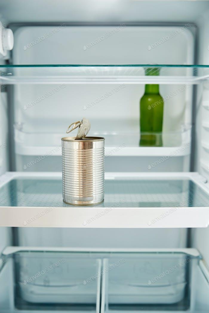 Ansicht Blick in den Kühlschrank leer außer für offene Blechdose und Flasche Bier auf Regal