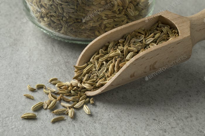 Heap of fennel seeds on a wooden spoon