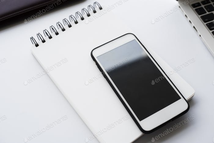 Closeup of empty screen mobile phone on notepad