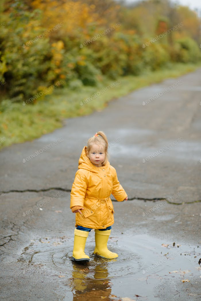 A little girl is jumping in a puddle in yellow rubber boots and a waterproof raincoat. Autumn Walk.