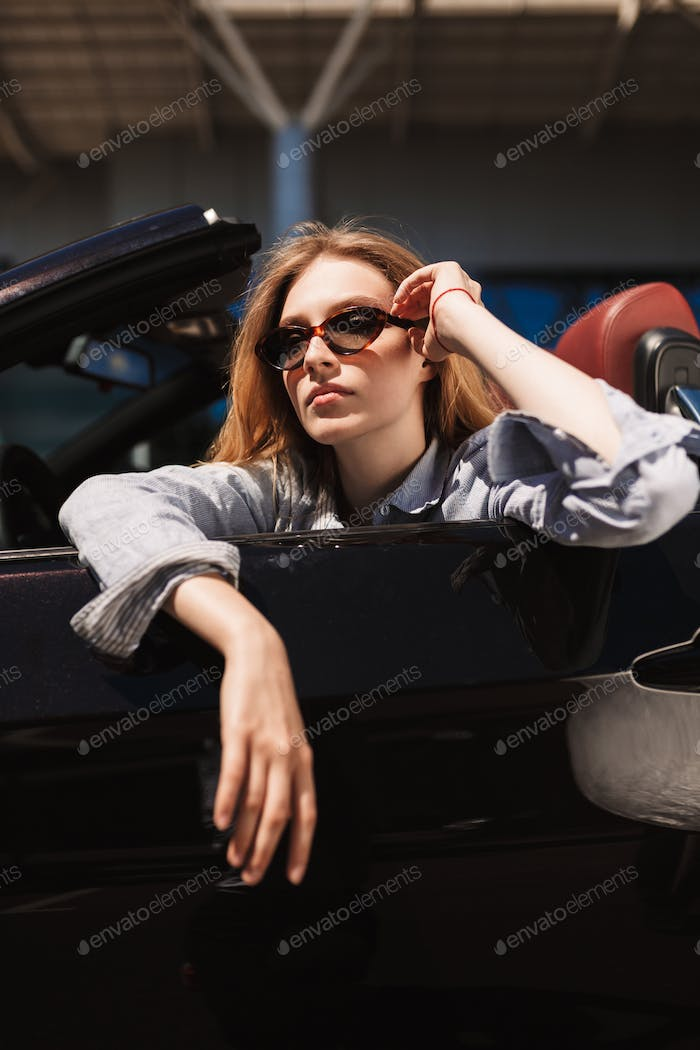 Beautiful girl in sunglasses in cabriolet car thoughtfully looki