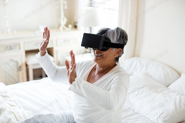 Senior woman using virtual headset on bed