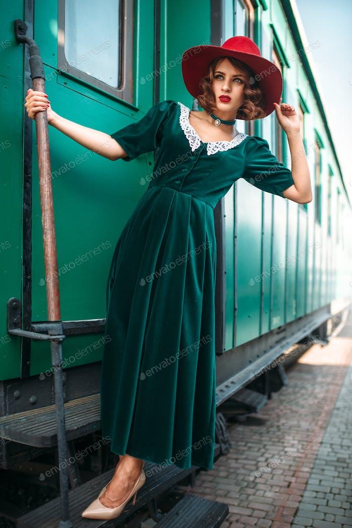 Frau im roten Hut gegen alten Eisenbahnwagen