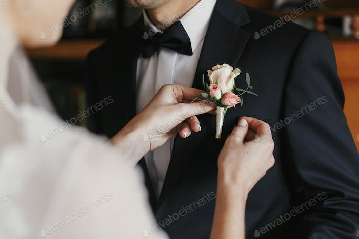 Bride putting on stylish simple boutonniere with roses on groom black suit