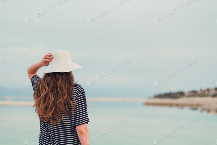 Young girl with shining blonde hair goes to seaside, Dead Sea beach. Travel, summer vacation