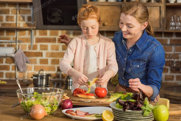 portrait of little daughter and mother making salad for dinner together at home