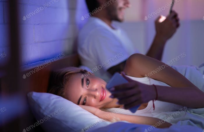 Millennial Couple Using Cellphones Lying In Bed At Home