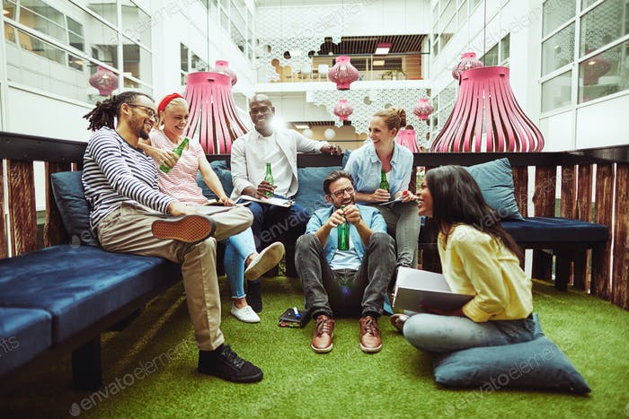 Diverse businesspeople sitting in an office lounge drinking beers together