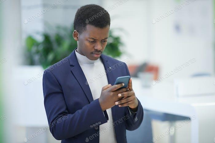Erfolgreicher afrikanischer Geschäftsmann hält Smartphone