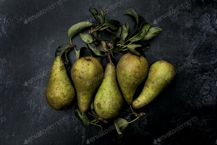 High angle close up of green pears on black background.