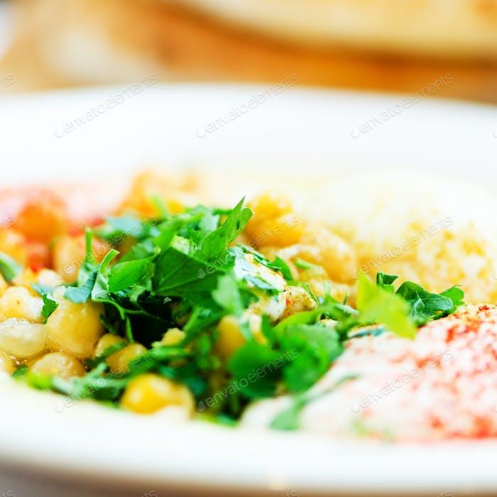 Klassischer Hummus mit Petersilie und Pita. Traditionelles jüdisches Essen und orientalische Küche Rezept