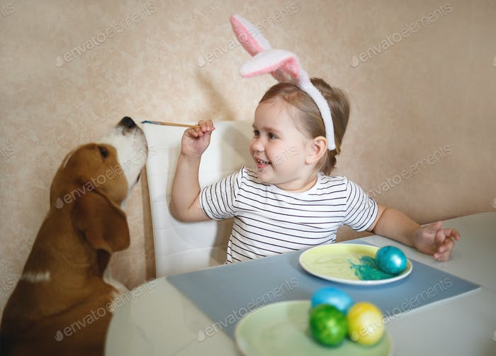 little cute blue-eyed girl and beagle puppy paint easter eggs