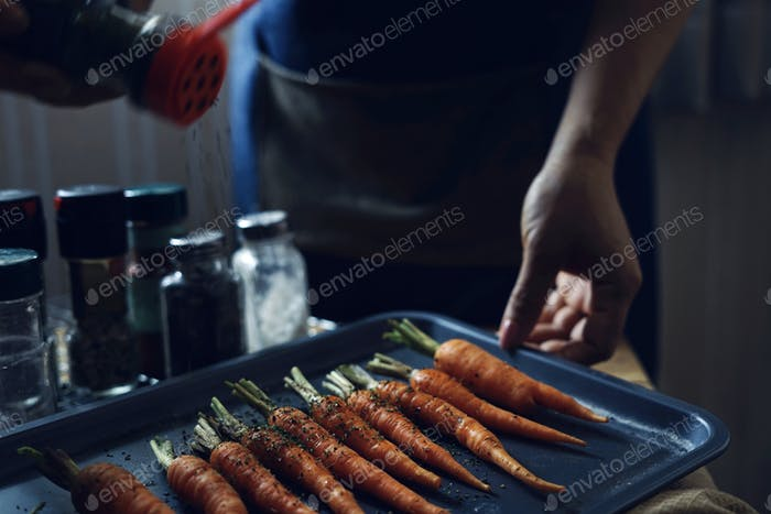 Chef sprinkle the seasoning on carrots