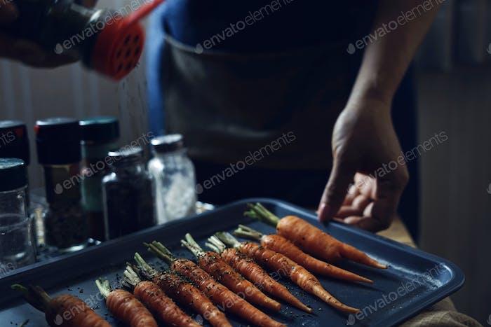 Chef bestreuen die Würze auf Karotten