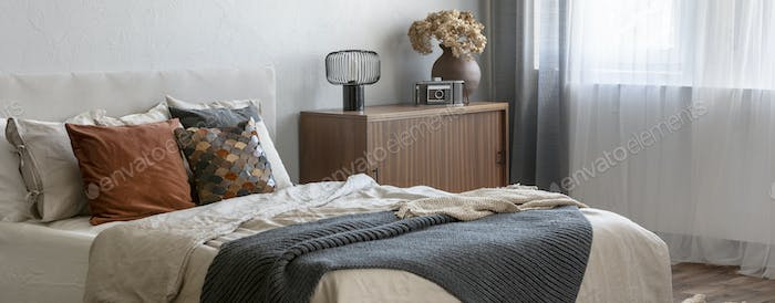 Vintage wooden cupboard next to king size bed with pillows and blanket in trendy bedroom interior