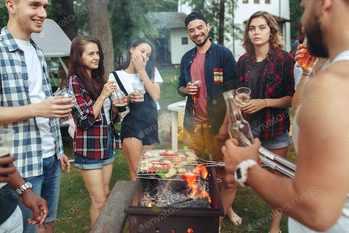 Gruppe von Freunden, die im Garten grillen. Konzept über gute und positive Stimmung mit Freunden