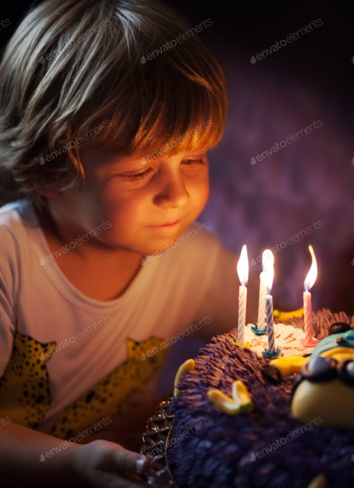 Little boy blows out candles on his birthday