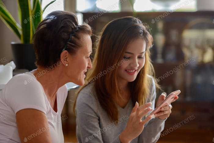 Two happy multi ethnic women using phone together at home