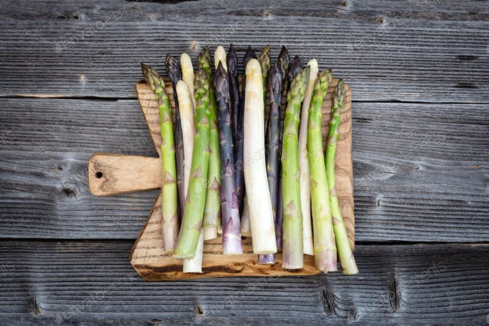 Green, purple and white asparagus sprouts