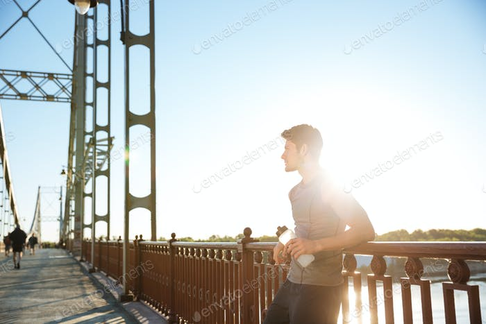 Sports man resting after running while leaning against bridge railing