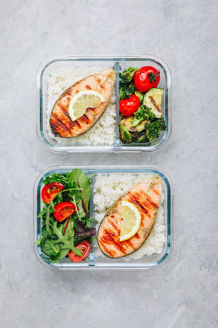 Meal prep containers with salmon and rice, green salad and baked vegetables.