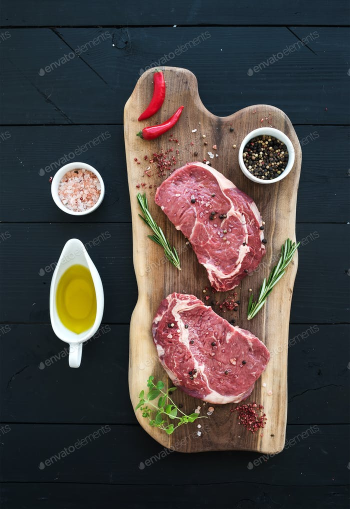 Raw fresh meat Ribeye steak entrecote and seasonings on cutting board over dark wooden background.