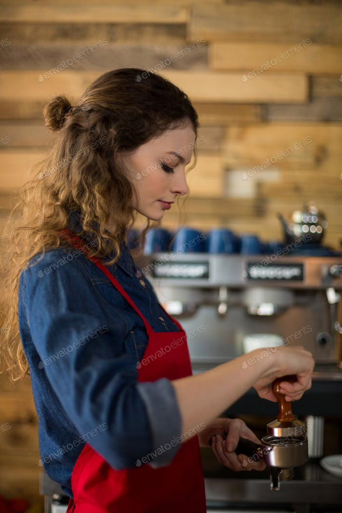 Waitress using a tamper to press ground coffee into a portafilter