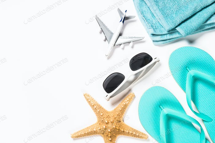 Blue flip flops, sunglasses, plane and starfish on white background