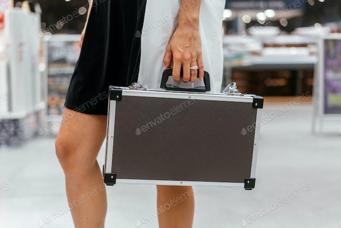 Das Mädchen hält ein kleines Aluminiumgehäuse