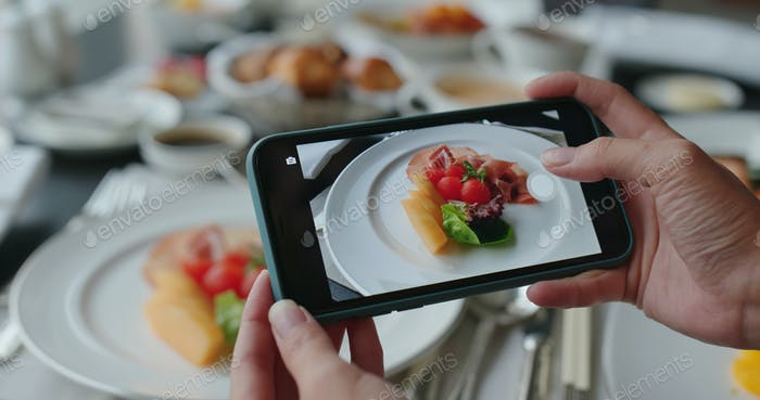 Woman use cellphone to take photo of the dishes
