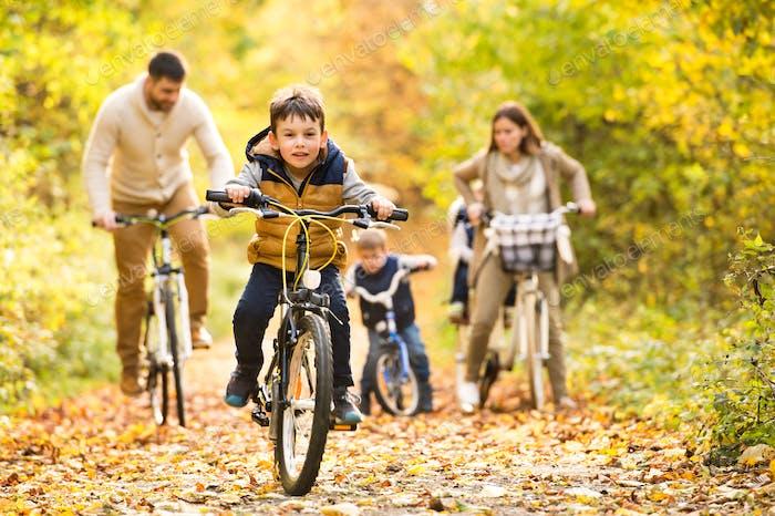 Junge Familie in warmen Kleidung Radfahren im Herbst Park