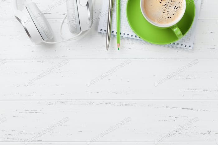 Office desk with coffee cup, headphones and supplies