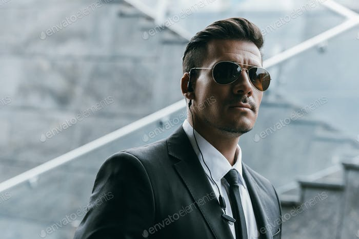 handsome security guard standing in sunglasses with security earpiece