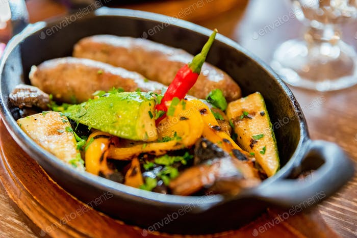 Grilled fried sausages kupaty on iron skillet grill with vegetables