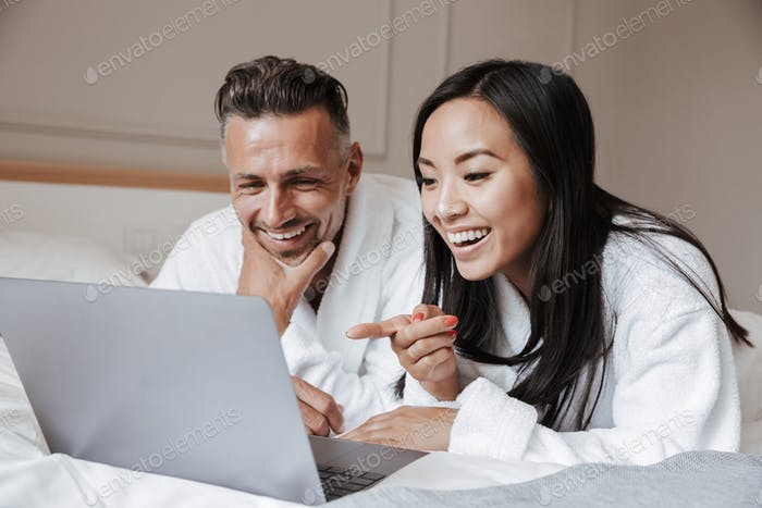 Happy young couple dressed in bathrobes lying on bed