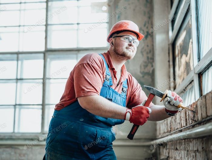 Plump professional worker strikes old plaster from brick wall