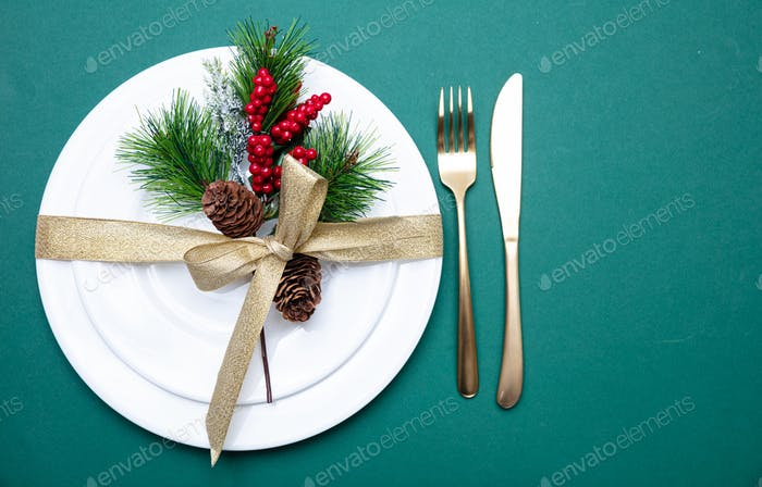 Xmas place setting. Gold cutlery and white set of dishes, green background