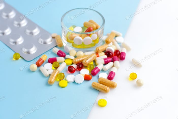 Assorted pharmaceutical medicine pills, tablets and capsules on blue and white background.