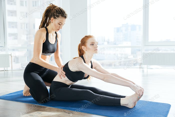 Woman sitting and stretching with her coach