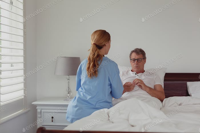 Caucasian female doctor talking to disabled active senior man about his hearing aid in bed