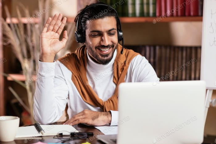 Young Indian Teacher At Laptop Computer Waving Hello At Home