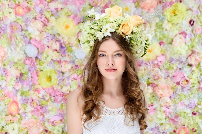attraktive junge Frau im Blumenkranz auf floralem Hintergrund