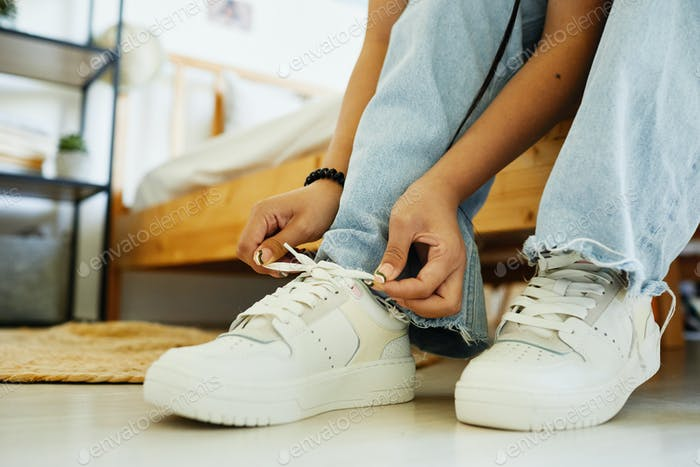 Girl Putting On Sneakers Close Up