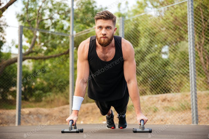 Handsome fitness man doing push-up exercises with sport equipment