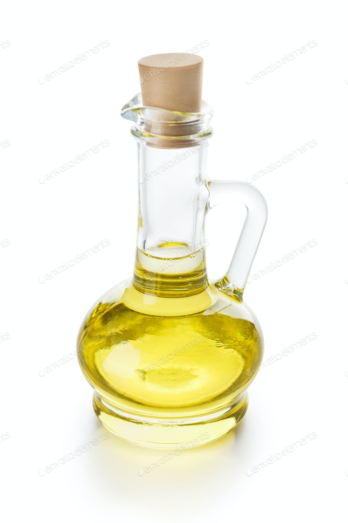 Olive oil in glass jug on white